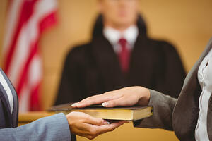 Witness swearing on the bible telling the truth in the court room for a long term disability litigation