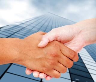 Close up of a business handshake with an office building behind.jpeg
